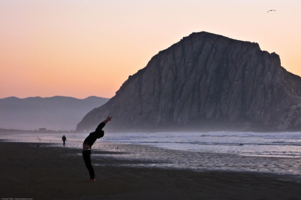 "Upward Salute – Urdhva Hastasana - Person performs mystical ""Sun Salutation"" yoga stretching exercise on Morro Strand ""Church of Kelp"""